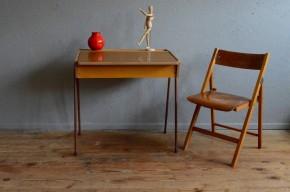 Avec ses fins pieds tubulaires, ses lignes modernistes et son plateau en formica voici un pupitre parfaitement typé de la décennie 1950 1960. Idéal pour un accompagner un enfant dans ses moments studieux ou créatifs, le bureau et la chaises forment un ensemble aussi cohérent que pratique.