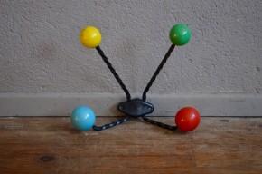 Quatre boules, quatre couleurs ! Ce joli porte-manteaux de la fin des années cinquante nous rappelle les modèles moléculaires des cours de chimie ! Le contraste entre le fer forgé noircis et les boules colorées est d'un effet saisissant ! Nous aimons son aspect simplement graphique et ses jolies couleurs franches.