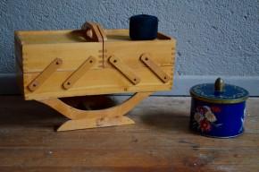 Formes modernistes et lignes graphiques pour cette mini-boîte à couture, travailleuse, ou boîte à ouvrage. Elle nous arrive des années 50 avec ses formes simples et la teinte miel du bois. Elle s'avérera pratiques avec ses nombreux espaces de rangement! On l'imagine aisément sur un joli bureau ou sur une commode de salle de bain! Ses dimensions réduites lui donnent un côté mignon et attachant ; elle deviendra une boite à bijoux vintage ou votre meilleur allié dans le rangement de vos accessoires de bricolage, couture ou scrapbooking !