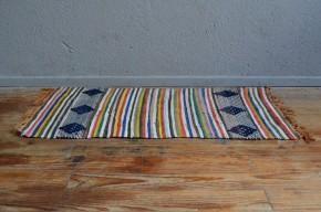 Plus finement travaillé que les tapis Chindi habituels, ce spécimen affiche de jolies couleurs et des motifs ethniques dans l'air du temps. Ancien et de belle facture, il est tissé de fils de coton et de soie. Dans l'entrée, une chambre enfant ou au pied du lit, ce tapis apportera de la couleur et complétera subtilement une déco bohème ou hippy chic!