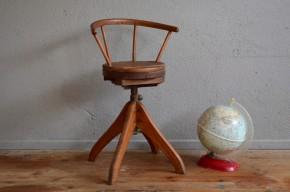 """Les suppositions quant à l'origine de cette chaise des années 40 fusent à l'Atelier! Meuble de métier, assis-debout d'horloger, fauteuil de coiffeur pour enfant, nous ignorons dans quel cadre cette splendide chaise pivotante a officié. Ce qui est certain en revanche, c'est que nous n'avions encore jamais vu pareil énergumène : piétement massif épais, système de réglage indus, belle finesse et lignes """"boomerang"""" élégantes du dossier-accotoirs en bois courbé... Splendide chaise de bureau enfant ou détourné en bel objet déco pour les plus grands, ce fauteuil vintage sera remarqué!"""