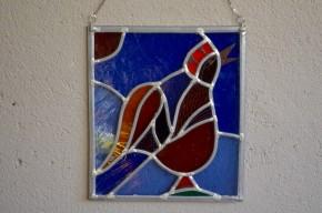Couleurs flamboyantes et joyeux dessin, cet ancien vitrail est plein de charme. Ce tableau original, résultat de l'utilisation de jolies matières et d'un travail minutieux, apportera une note bohème pétillante et décalée. Posé devant une fenêtre, le verre coloré dans la masse dévoilera tout son caractère et créera une atmosphère chaleureuse.