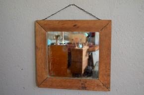 Ce miroir ancien possède un cadre Louis Philippe en bois massif. Sa forme géométrique et rigoureuse est adoucie par la patine et l'aspect chaleureux du bois. Une fine chaînette permet sa suspension.