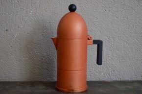Cette cafetière à l'italienne a été dessinée dans les années 80 par Aldo Rossi. Elle est fuselée comme un obus, adoucie par le traitement cuivré mat du métal. Avec sa poignée en plastique noir et la petite boule qui la surmonte, elle a une petite allure enfantine qui n'est pas sans rappeler la fusée de Tintin ! Ce modèle culte est baptisé « La Cupola » par Alessi.