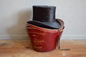 Ancien accessoire de mode masculine, cet ancien chapeau haut de forme est un objet aussi décoratif qu'historique. Nous les avons trouvés ensemble mais la boite correspond à un chapelier de Colmar et le chapeau d'un Sélestat. Les écritures en allemand et les orthographes des communes nous permettent de dater ces objets à la période d'annexion de l'Alsace Lorraine, soit fin 19e début 20e siècle. Le chapeau possède de magnifiques reflets brillants, et une forme aussi haute qu'élégante !