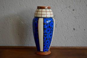 Ce joli vase en céramique craquelée est une production Belge époque art déco. Sorti des ateliers  Auguste Mouzin & Cie à  Wasmuel il possède des caractéristiques typiques de cette fabrique : Des émaux colorés, en blanc, bleu et beige à l'aspect coquille d'oeuf. Nous aimons le dynamisme de sa forme et la fraîcheur de ses couleurs.