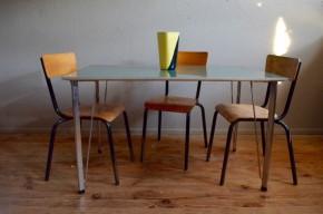 """Arne Jacobsen est un architecte et designer Danois des plus marquants. Très marqué par les propositions fonctionnalistes de l'école allemande du Bauhaus, il adoucira les lignes pour proposer ce qui deviendra le design organique scandinave. Il associe avec brio le métal et le bois (massif, mélaminé ou contreplaqué) dans ses créations, en offrant toujours des formes simples, des lignes claires évidentes, mais empreintes de douceur. Cette table de repas rectangulaire, création midcentury, a été éditée et fabriquée par Fritz Hansen. Les formes sont simples, idéales et tournées vers la fonction, mais des détails apportent de la rondeur et de la convivialité au trait. Les pieds en acier chromé, à sabot de bois noir, sont élancés avec un élégant rappel oblique. Le plateau """"vert mélèze"""" est lui, effilé au maximum sur sa tranche et possède un chant en métal brossé argenté rappelant le piétement."""