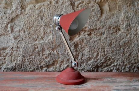 """Dans les années 50, on assiste à une arrivée des couleurs vives dans les intérieurs. Les lampes """"cocotte"""" viennent révolutionner les bureaux avec leurs formes arrondies, fuselées, aérodynamiques et leur peinture vive. Ce joli spécimen est doté de deux rotules pour s'orienter dans toutes les directions et adapter l'éclairage à toutes les conditions! Nous apprécions ses lignes volontaires et dynamiques, ainsi que sa peinture rouge à l'effet texturé."""