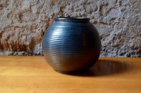 Ce joli vase boule est le fruit de la poterie Echinger. Sa forme géométrique et sobre est mise en lumière par les fameux émaux noir à l'aspect à la fois brillants et mats caractéristiques. La forme sphérique du vase est finement mise en valeur par les décors annelés. La pièce est signée en creux sur le dessous.