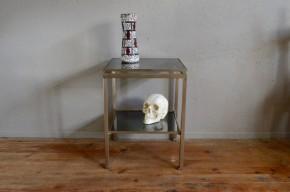 Guy Lefevre est un designer français qui travaille le mobilier à la façon des orfèvres. Jouant sur les brillants et les mat des métaux, les transparence il propose un dessin d'une grande rigueur, d'une sobriété élégance et classieuse. Ce bout de canapé est édité par la prestigieuse Maison Jansen dans les années soixante dix. Réalisé en acier brossé, le guéridon possède deux plateaux en verre fumé. Son design est simple, ses proportions subtiles ; un léger espace de vide situé sous le plateau lui renforce son élévation verticale et les jeux avec la lumière.