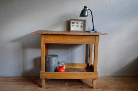 Simple et atypique, ce meuble de métier ancien date des années 40 et semble ne jamais être sorti de son atelier. La structure est en bois couverte d'une patine à la bière très ancienne pour un effet trompe l'oeil veiné très lumineux. Le plateau est brut, constitué de grosses planches patinées par une vie de labeur et divinement lustrées par les années! Pratique en desserte dans un atelier ou détourné en console de salon en y improvisant un petit jardin d'intérieur, ce meuble indus rétro a de l'allure et la trempe d'une pièce vintage unique, comme on les aime!