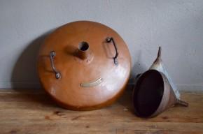 Ce chapiteau d'alambic est un objet de métier aussi surprenant qu'attachant. Cette pièce sculpturale est située au dessus du cucurbite et concentre les vapeurs d'alcool vers le col de cygne. De belles dimensions et avec sa patine d'usage cuivrée, voici une pièce de décoration liée à l'histoire de l'Alsace. Marc de Gewurztraminer, schnaps, eau de vie de mirabelle et poire, fine; sans aucuns doute ce bel objet connus moult effluves parfumées et alcoolisés.