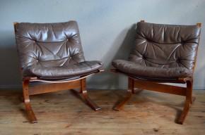"""Ingmar Relling a imaginé ces fauteuils dans les années 60. Ce créateur norvégien, adepte d'un design minimaliste, nous propose un magnifique exemple de l'alliance réussie entre forme épurée et grand confort. Le nom de cette série de fauteuils est même très évocateur """"Siesta"""". Fauteuil lounge et scandinave, à l'assise redressée mais moelleuse, c'est un fauteuil de détente, idéal pour la lecture ou la conversation, mais également parfait pour un petit somme réparateur. Le piétement confère à ce fauteuil d'exception, une souplesse appréciable ainsi qu'un look scandinave identifiable. Nous disposons de deux fauteuils identiques, le cuir possède de jolis reflets grisés."""