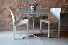 Arne Jacobsen est un architecte et designer Danois des plus marquants. Très marqué par les propositions fonctionnalistes de l'école allemande du Bauhaus, il adoucira les lignes pour proposer ce qui deviendra le design organique scandinave. Il associe avec brio le métal et le bois (massif, mélaminé ou contreplaqué) dans ses créations, en offrant toujours des formes simples, des lignes claires évidentes, mais empreintes de douceur. Cette petite table carrée, création midcentury, a été éditée et fabriquée par Fritz Hansen. Les formes sont simples, idéales et tournées vers la fonction, mais des détails apportent de la rondeur et de la convivialité au trait. Le piétement étoile est élégant et très pratique, libérant l'espace. Le plateau « vert mélèze » est lui, effilé au maximum sur sa tranche et possède un chant en métal brossé argenté rappelant le piétement.