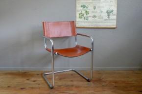 Ce fauteuil iconique du design italien date des années 1970. Hommage aux productions du Bauhaus, il mise sur le contraste des matières, le cuir et le chrome, dans un design ingénieux et élégant. L'assise en porte-à-faux allège le dessin et offre, cerise sur le gâteau, une assise tout en souplesse. Nous aimons le contraste entre le brillant minéral du chrome et la chaleur du cuir couleur fauve. Fauteuil de bureau par excellence, nous l'imaginons également en confortable assise de bout de table.