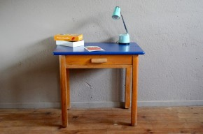 """Voici un bureau enfant des années 50 au look rétro simple mais très efficace. En bois massif, il est lumineux et affiche des petits détails plein de douceur et de charme. Le petit tiroir ravira les bambins qui aura sous la main ses premiers outils d'artiste! Le plateau rénové """"bleu égyptien"""" réveille cette petite pièce vintage, promesse de moments de folie douce..."""