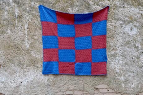 Cette petite couverture faite-main est en laine. L'assemble de carrés de tricot bleu et bordeaux est minutieux et joyeux! Parfaite pour réchauffer les petons dans le landau ou le berceau, le plaid rétro apportera une touche bohème posé sur le canapé ou le rocking-chair en rotin!