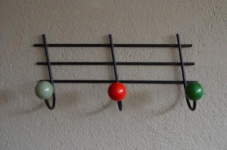 """3 boules de bois de 3 couleurs différentes! Ce porte-manteaux rétro date des années 50 et nous fait penser à 3 croches facétieuse sur une portée musicale endiablée ! Le contraste entre le fer forgé noir et les boules colorées est dynamique ! Nous aimons son aspect simplement graphique et ses jolies couleurs pop. """"Trois petites notes de musique ont plié boutique..."""""""
