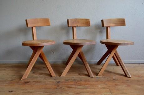 """Sûrement en référence au mobilier traditionnel voire rustique, la chaise S34 dessinée le designer Pierre Chapo est minimaliste, jouant sur la matière brute et la sobriété des lignes. En orme massif, son piétement en faisceau évoquant un jeu de mikado est élégant et très original. Quant au dossier déporté, il accroche l'œil et rendent les lignes de cette chaise unique. On retrouve là ce qu""""on affectionne tant chez Chapo : l'originalité des assemblages, la beauté des matières... et un grain particulier reconnaissable entre 1000!"""