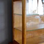 Ce meuble au lustre somptueux semble suspendre le temps! Son origine nous est inconnue mais ce meuble de métier a probablement œuvré dans un petit commerce, une mercerie ou une épicerie. En bois massif patiné, sa teinte dorée, ses angles arrondis et la corniche discrètement travaillée apportent beaucoup de douceur et affinent les traits de ce meuble des années 40. Composé d'une partie vitrée et d'un compartiment bas fermé par des portes coulissantes, il allie esthétique et praticité. Dans le salon ou la cuisine, nous l'imaginons cabinet de curiosité original ou vaisselier authentique! Voilà un meuble ancien unique en son genre!