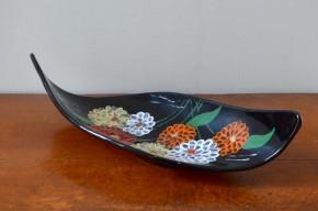 Dimension généreuses, formes libres et sculpturales, contrastes et couleurs saisissantes sont les qualité de cette large coupe mid-century. Production de la célèbre faïencerie de Longwy, c'est un modèle de belle taille, qui témoigne d'un savoir faire artisanal et d'un joli sens de l'esthétisme. Vide poche, corbeille à fruits ou simplement objet décoratif elle saura attirer l'œil et donner une touche fleurie dans un bel intérieur.