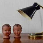 """Dans les années 50, on assiste à une arrivée de formes nouvelles dans le design des luminaires. Les lampes """"cocotte"""" viennent révolutionner les bureaux avec leurs formes arrondies, fuselées, aérodynamiques et leurs design résolument modernes. Répondant aux exigences du concept de modularité en vogue à cette période, cette petite lampe peut être utilisée en applique ou à la verticale. Nous aimons son design tonique, le traitement élégant de la couleur en noir et doré."""