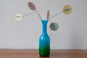 La verrerie d'art d'Ekenas Sweden a été fondée en 1917 par des verriers passés par les ateliers d'Orrefors. Ce vase scandinave est une pièce de John Orwar Lake, en forme de bouteille à col élancé et evasé. Le traitement des couleurs est vraiment caractéristique du travail de l'artisan. Le vert se lie au bleu, dans un élan spiralé qui renforce la légèreté et la verticalité de la pièce. La présences de  nombreuses bulles dans le verre apporte une touche supplémentaire de nuancée et de jeux lumineux.