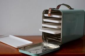 Nous avons fait la découverte de cette curieuse valise en métal au Danemark. Il s'agit de la version rétro d'un objet du quotidien que tout le monde connaît bien là bas : la boîte à lunch. 5 plateaux coulissants permettent d'emporter au bureau ou en pique-nique Gudhjemmadyppa, Smørrebrød et autres spécialités scandinaves, et même de régaler les amis au passage! Sa poignée en cuir épais et patiné, et la box en métal vert givré nous ont séduits. On aime l'idée de détourner cet objet insolite en boîte à bijoux!