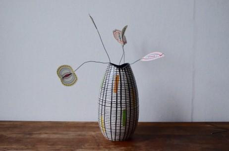 Joli trait décoratif minimaliste pour ce joli vase midcentury! Il est orné de taches de couleur abstraites mises en relief par un email texturé et rayé de lignes noires. Très sobre, c'est une belle pièce déco vintage.
