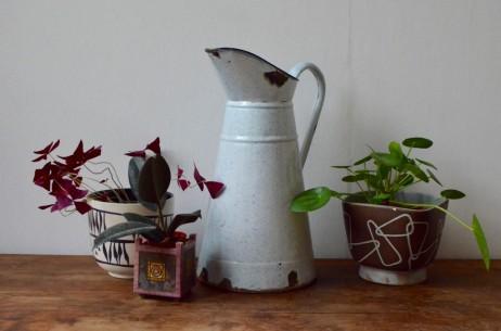 Objet usuel et accessoire domestique des années 30, ce broc à eau était utilisé lors de la toilette avant l'arrivée de l'eau courante. De grande dimension, le pot à eau est émaillé et dispose d'une bec verseur et d'une poignée. Nous aimons son air bohème et le charme de ces pièces vintage authentiques. Nous imaginons aujourd'hui ce pichet devenir vase pour bouquets des champs ou hautes fleurs, ou arrosoir atypique...
