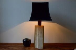 Cette lampe brutaliste des années 70 s'affiche sculpturale massive et sans concession. Le pied en béton ou travertin ??? est d'une géométrie rigoureuse, épaisse, à peine adoucie par des cornières dorée. C'est finalement de son aspect brut qu'émerge la poésie et l'esthétisme, ce qui fait de ce luminaire une pièce déco un peu à part. Lampe de table et pièce de design exigeant, elle saura apporter une touche de lumière dans une ambiance feutrée.