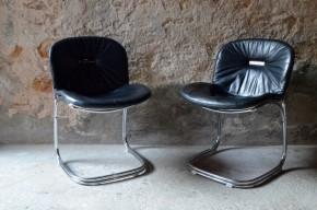 """Joli duo de chaises chromées dessinées par Gastone Rinaldi baptisées Sabrina par le designer italien lui-même ! Elles côtoient Dafné, Letizia, Zeta, Aurora dans les annales créatives de l'architecte. Ce dernier utilisera les possibilités offertes par le fil d'acier chromé pour proposer des assises aux formes audacieuses et aux transparences rythmées. L'assise des chaises Sabrina est en effet soutenu par un important porte-à-faux qui offre un confort très souple et aérien. Très typées du design italien seventies, voluptueux, haut de gamme et original, ces chaises Sabrina sont tout simplement """"bellissima"""" ! Et cerise sur le gâteau, elles sont toutes deux accompagnées de leur superbe coussin de cuir lisse noir pour encore plus de confort et d'élégance!"""
