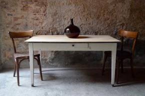 Cette table toute simple des années 30 est un bel exemple de l'attachement que peut générer un objet, des émotions que peut procurer un meuble chargé d'histoire. Impressionnante d'authenticité, cette table de ferme en bois réveille les souvenirs. On se souvient presque des soupers du soir, des ateliers gâteau, des parties de pâtes à modeler avec les plus petits et des instants thé avec les amies... Patine somptueuse et plateau en planches de sapin brutes, elle dégage une simplicité rustique aux accents bohèmes. Son piétement élégant blanc est rehaussé de patins peints gris, rappelé au niveau du chant du plateau. Un petit tiroir compartimenté ajoute encore un peu de charme à cette pièce rétro. Dans la cuisine ou devenue bureau, cette table apportera une douceur folle... et peut-être même un souffle de liberté!