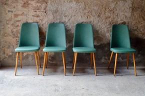 """Arrivées directement des sixties, voici une paire de chaises confortables, au caractère bien trempé. Skaï épais vert pop, piétement fuseau en bois massif de teinte claire et dossier forme """"tonneau"""" apportent une personnalité folle et assumée à ces chaises cocktail rétro. Celles-ci révèlent encore une jolie surprise à l'arrière : dossier clouté pour un look rockabilly comme on aime... Let's dance!"""