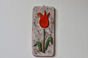 Cette charmante plaque en céramique décorative nous vient de la poterie Ernewein à Marmoutier. Réputés pour leurs productions de pièces de forme colorées, notamment de nains de jardins émaillés tous plus beaux les uns que les autres. Ce travail reprend le motif de la tulipe cher au potier qu'il va stylisé et mettre en couleur et en relief grâce à un émaillage nuancé et vivant. Voici une jolie pièce de décoration murale.