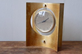 Hour Lavigne est une fabrique française réputée de montres et horloges. Cet atelier est à la frontière entre l'art et l'artisanat. Hour Lavigne fabrique les mécanismes horlogers mais procède également à l'habillage de ceux ci. Cette horloge ancienne possède un design épuré, organisé autours de formes géométriques évidées. Le cadran et le mécanisme est suspendu par deux lames de métal incurvées. Il pivote autour d'un axe.