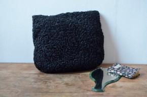 Ce sac manchon des années 30 est sublime et en parfait état. C'est un accessoire de mode étonnant et décalé mais doté d'une élégance surannée. En Astrakan noir, il est de grand style, témoin du faste des années folles. De taille moyenne, il intègre un manchon très chaud en satin noir.