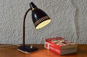 clairez votre bureau à l'aide d'une jolie lampe vintage! Ce beau modèle de luminaire nous vient des années soixante et nous adorons son design : des lignes fluides, souple aux arrondis étudiés. Cerise sur le gâteau son déflecteur est ajouré, la lampe de travail peut alors se muer en lampe d'ambiance diffusant une douce lumière. Ce modèle est de belle facture, la peinture profondément noire contraste avec de petits éléments dorés.
