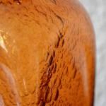 Chiné au Danemark, ce vase est réalisé en verre soufflé. Belle pièce artisanale, les imperfections et variations du verre orangé, et la multitude de bulles viennent jouer avec la lumière pour de jolis effets.