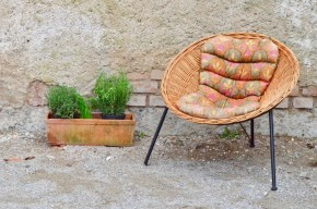 """Les lignes de ce fauteuil en osier des années 70 sont captivantes et attirantes. L'assise de forme corbeille est superbement travaillée, rappelant les loveuses ou les lignes des célèbres """"Acapulco"""". La chaleur et la douceur du rotin est réveillé par le contraste du piétement tubulaire noir. Et, comme une pépite inattendue, apportant une note colorée et un confort supplémentaire, le fauteuil a conservé son coussin au tissu vintage graphique et vitaminé!"""