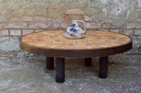 Table basse culte des années 60, ce modèle au plateau rond est signé Roger Capron pour Vallauris. Il présente une structure en lames de bois appareillées et un plateau à décor de carreaux. Les motifs végétaux, entre rusticité et douce originalité, sont le fruit d'un joli travail d'estampage. Dans un intérieur nature ou wabi-sabi, cette table basse aura une jolie présence.
