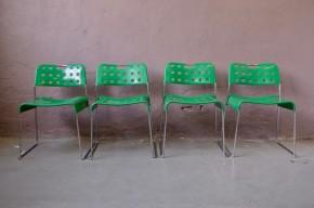 """Dessinées par Rodney Kinsman dans les années 70, la chaise Omkstack estr rapidement devenue une icône du design anglais. Simples, ses lignes sont légères et misent avant tout sur la fonctionnalité. La finesse du piétement cintré d'une seule pièce, et la robustesse du dossier et siège en tôle pressée ajourée, tiennent à l'utilisation de matériaux performants et à une conception remarquable. La chaise Omkstack a véritablement marqué son temps, de par sa qualité et ses innovations techniques, et une production record! Voilà pourquoi elle figure dans les collections des grands musées de design... Quant à nous, nous sommes tombés amoureux de cette laque """"vert sinople"""" peu courante et totalement décoiffante de la série de 4 chaises Omkstack éditées par OMK !"""