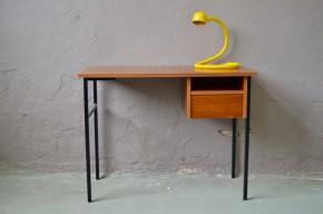 Ce bureau rétro tout en finesse et légèreté séduit par sa simplicité et ses jolies manières. L'association du teck à la teinte chaleureuse et du métal traité avec finesse est harmonieuse et intemporelle. Les lignes modernistes de ce bureau vintage sont minimalistes, et pourtant, toues les critères pour en faire une parfaite table d'études sont réunis : grand plateau, tiroir, niche et bel espace pour y glisser un confortable fauteuil. Associé à une lampe pimpante, ce joli meuble des années 60 conviendra à tous, sans limite d'âge.
