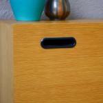 Joli pour de cœur pour ce meuble bas des années 60. Son caisson minimaliste en bois blond s'ouvre sur un bel espace de rangement, fermé par une porte à abattant. Rythmée par 4 poignées en épais plastique noir qui répondent avec discrétion au piétement fuseau, cette petite enfilade sixties a du panache. Le contraste des matières et des couleurs, les finitions de belles qualités feront de ce sideboard vintage aux allures modernistes un parfait meuble TV ou Hifi, permettant de ranger la partie technique pour ne mettre en valeur que l'essentiel!