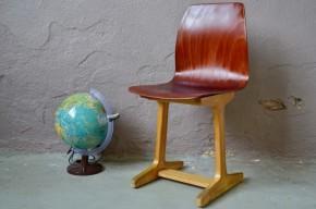 """Mobilier scolaire à l'origine, cette chaise rétro a été dessinée par Adam Stegner dans les années 50 et éditée par  Pagholz Flötotto. On aime beaucoup le contraste des couleurs, des formes et des matières. La coque """"Teck"""" est en Pagwood®, matériau innovant permettant d'allier finesse formelle, confort et solidité. Ancienne pièce de mobilier scolaire, son design doux et accueillant feront de cette chaise """"LA"""" chaise de bureau parfaite pour les enfants et adolescents."""