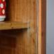 """Avec ses lignes modernistes, cette enfilade des années 60 est un meuble rétro au charme certain. Son grand caisson à étagères permet beaucoup de rangement, tout en présentant curiosités et jolis objets. Les portes coulissantes en verre allègent cependant les lignes en dynamisant le meuble et en jouant sur la transparence. Deux petits tiroirs agrémentent encore la partie rangement de ce bahut. Avec leur petit bouton """"diabolo"""", ils ajoutent au charme sixties du meuble et proposent une belle transition entre le caisson vitré et le piétement fuseau. Commode d'entrée, vaisselier ou enfilade pour le salon, ce meuble vitrine allie joliment praticité et convivialité."""