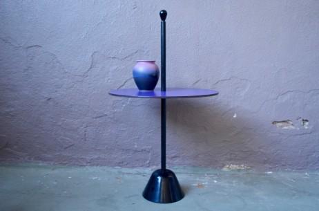 """Servomuto est une drôle de petite table dessinée par Achille et Pier Giacomo Castiglioni pour l'éditeur Zanotta. Cette desserte dont le projet remonte à 1974 est pensée comme un objet nomade, inclassable et modulable. C'est la petite table à tout faire, porte revue, bout de canapé ou chevet ... que l'on transporte au grès des envies et besoins dans toutes les pièces de la maison grâce à sa tige en acier laqué. Servomuto fait partie de la famille des petits meubles """"Servi"""" imaginée par les designers milanais. On y retrouve une déclinaison de productions innovantes adaptées au habitation modernes, utiles, fonctionnelles, minimalistes ludiques et modulables... On profite de toute cette originalité utilitariste dans cette version de Servomuto, dont le plateau peut être adapté à la déco de chaque pièce ou à l'humeur du moment."""