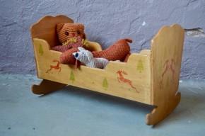 D'inspiration Waldorf ou Montessori, ce joli lit de poupée en bois affiche avec beaucoup de tendresse ses lignes et motifs rétro et rustiques. Ce petit berceau à bascule, destiné aux poupons date des années 60 mais il séduira à coup sûr les bambins des années 2010. Et, petite touche finale qui nous plaît tant : petit édredon et oreiller d'origine agrémentent ce charmant jouet... Doudou et petits baigneurs passeront une douce nuit!