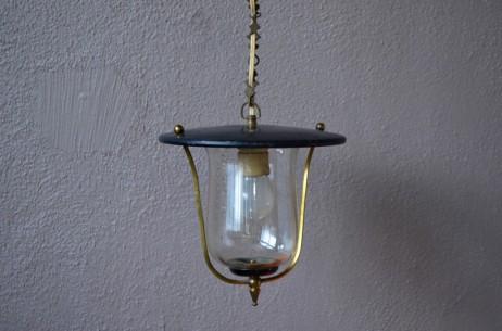 Le design de cette charmante petite lampe est une déclinaison de la lanterne traditionnelle dynamisée à la sauce midcentury. Le contraste entre la tôle peinte, le laiton et la transparence du verre est des plus charmant. Nous aimons ses formes modernistes, joueuses et ses finitions soignées. Elle fera mouche dans une entrée, un patio ou un couloir en y diffusant sa lumière vintage.