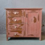 """Petit bahut ou commode ancienne des années 20, son charme élégant et rustique à la fois est rehaussé d'une peinture ancienne """"vieux rose"""". On est fan de son vécu unique et des dimensions réduites qui en feront aussi bien une commode pour le tout-petit qu'un meuble d'appoint dans une cuisine ou une salle de bain."""